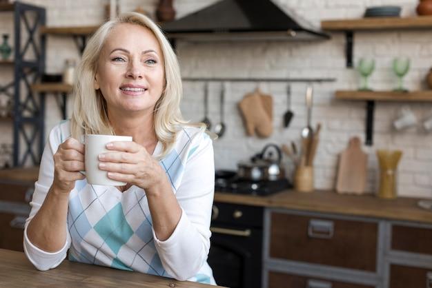Mittlere schussfrau mit kaffeetasse in der küche