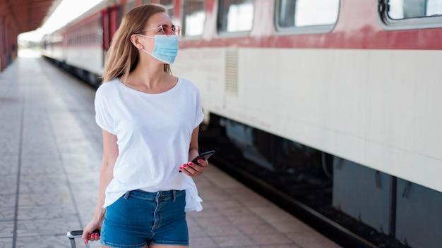 Mittlere schussfrau mit maske, die entlang zug geht