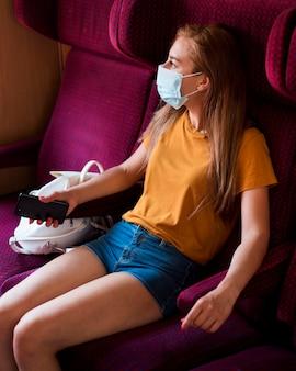 Mittlere schussfrau mit maske, die im zug sitzt