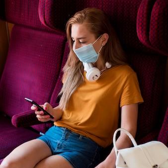 Mittlere schussfrau mit maske im zug