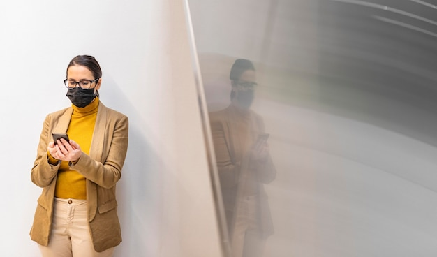 Mittlere schussfrau mit maske und telefon
