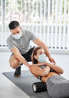 Mittlere schussfrau mit personal trainer