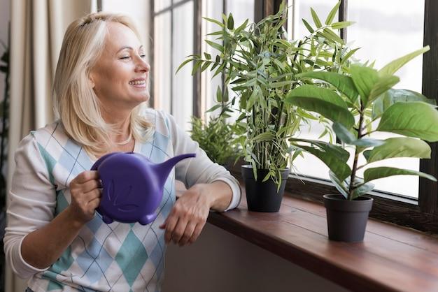 Mittlere schussfrau mit purpurroter gießkanne