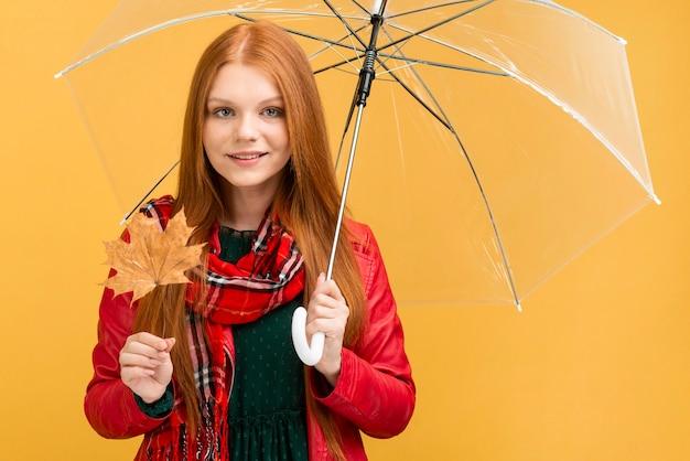 Mittlere schussfrau mit regenschirm und blatt