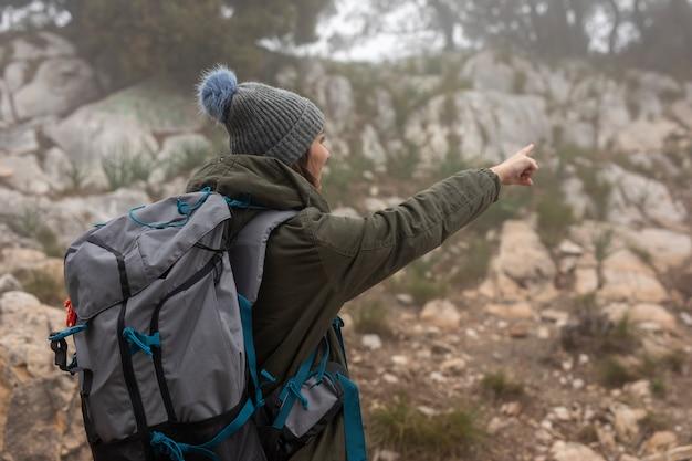 Mittlere schussfrau mit rucksack in der natur