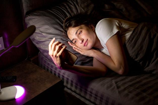 Mittlere schussfrau mit smartphone im schlafzimmer
