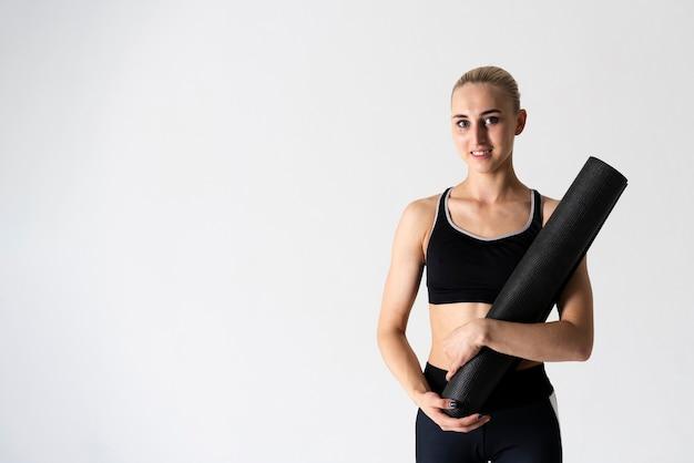 Mittlere schussfrau mit yogamatte und kopieraum