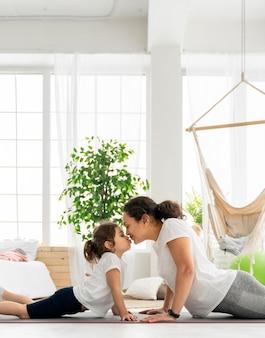 Mittlere schussfrau und kind auf yogamatte