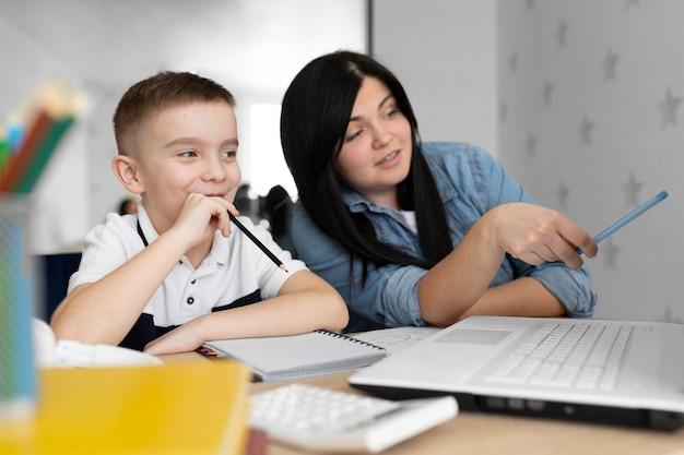 Mittlere schussfrau und kind mit laptop