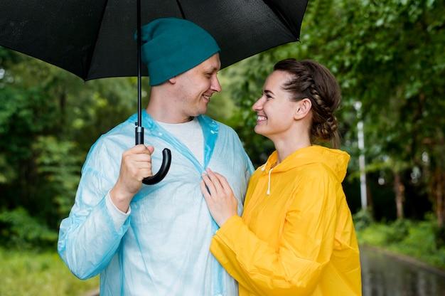 Mittlere schussfrau und mann, die sich unter ihrem regenschirm ansehen