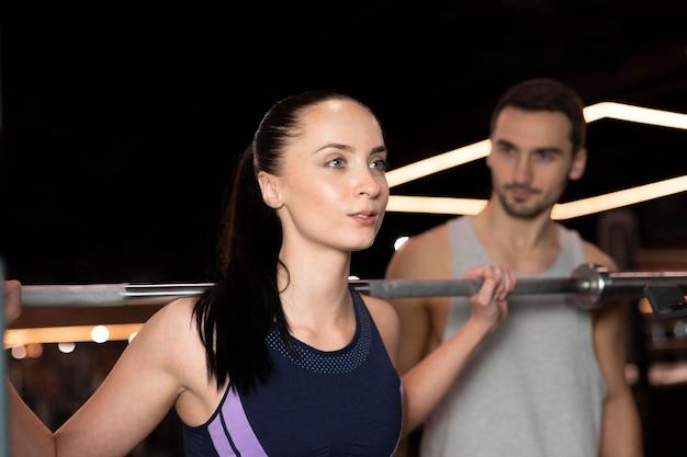 Mittlere schussfrau und -mann im fitnessstudio