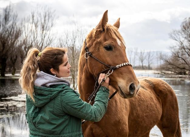 Mittlere schussfrau und pferd im freien