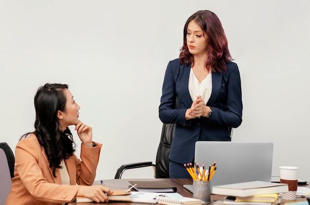 Mittlere schussfrauen beim treffen mit laptop