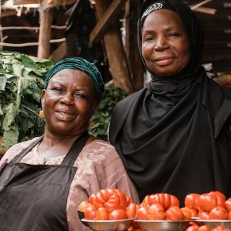 Mittlere schussfrauen, die am markt aufwerfen