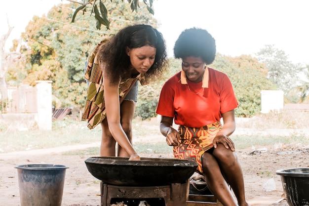 Mittlere schussfrauen, die draußen kochen