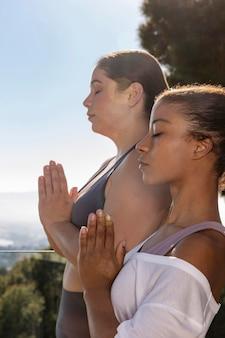 Mittlere schussfrauen, die draußen meditieren