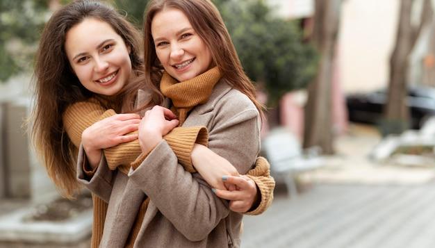 Mittlere schussfrauen, die draußen umarmen