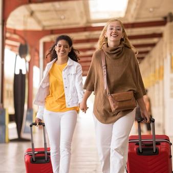 Mittlere schussfrauen, die gepäck tragen