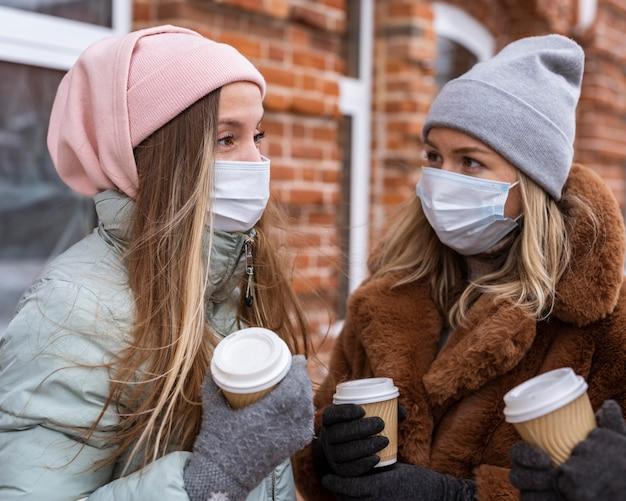 Mittlere schussfrauen, die kaffeetassen halten