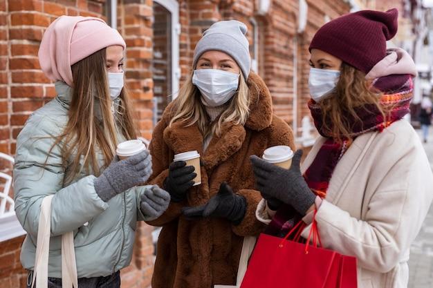 Mittlere schussfrauen, die medizinische masken tragen