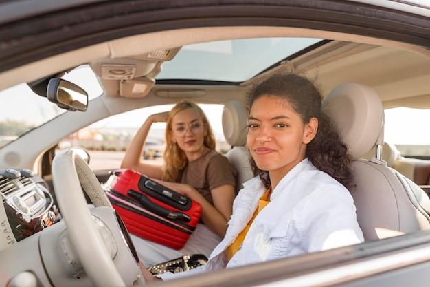 Mittlere schussfrauen, die mit dem auto reisen