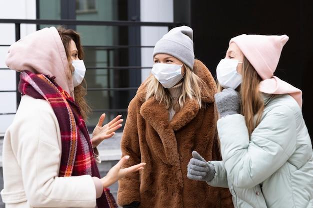 Mittlere schussfrauen, die schutzmasken tragen