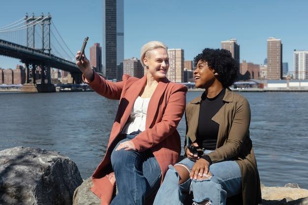 Mittlere schussfrauen, die selfie im freien nehmen
