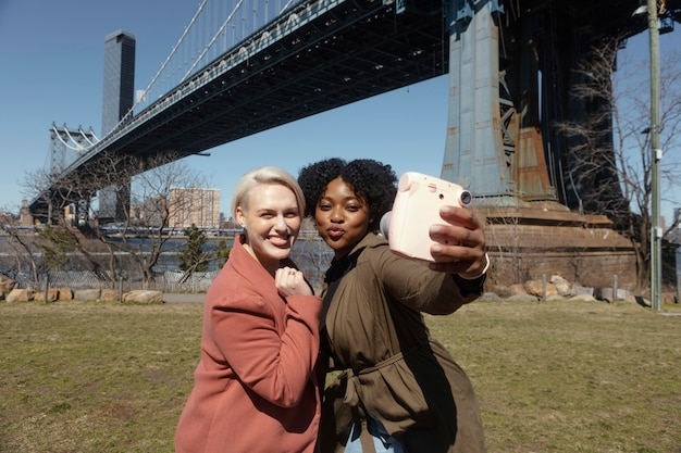 Mittlere schussfrauen, die selfies im freien nehmen