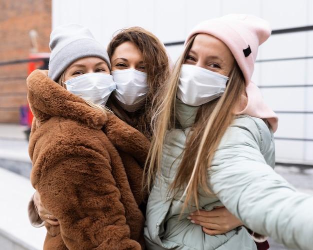 Mittlere schussfrauen, die selfies mit maske nehmen