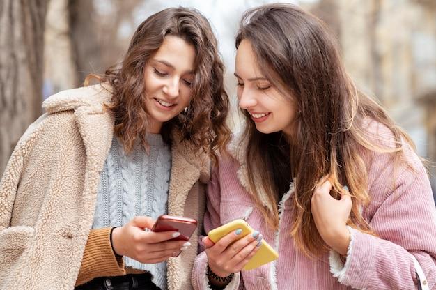 Mittlere schussfrauen, die smartphones halten