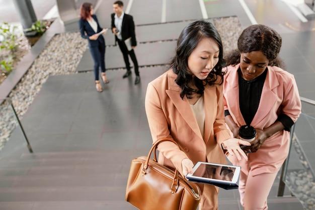 Mittlere schussfrauen, die tablette betrachten