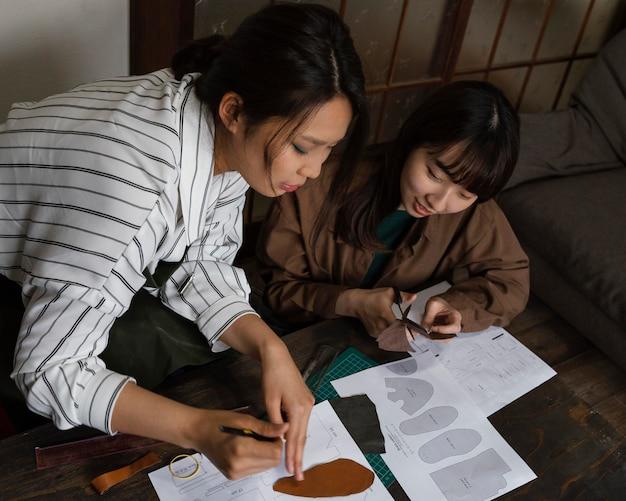 Mittlere schussfrauen, die textil schneiden