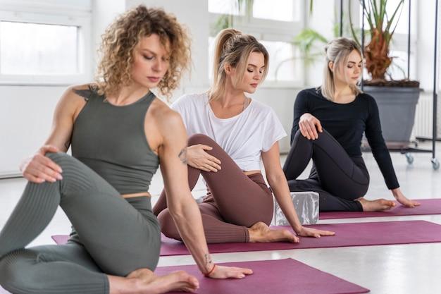 Mittlere schussfrauen, die yoga auf matte tun
