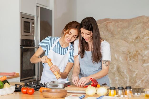 Mittlere schussfrauen, die zusammen kochen