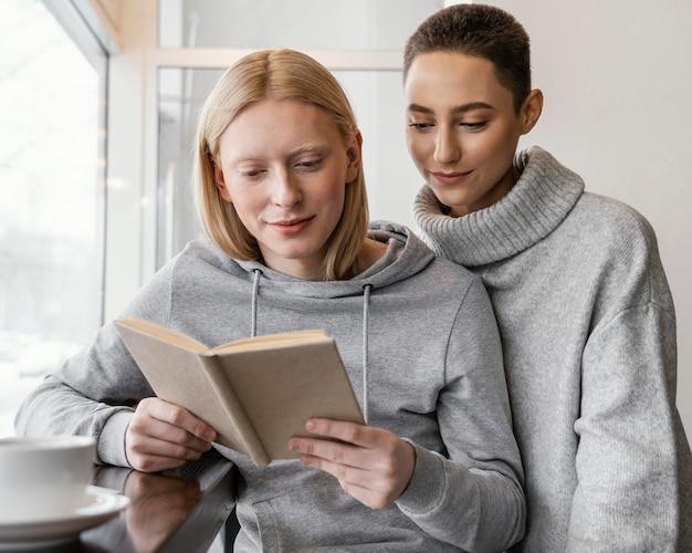Mittlere schussfrauen, die zusammen lesen