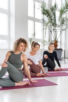 Mittlere schussfrauen, die zusammen yoga machen