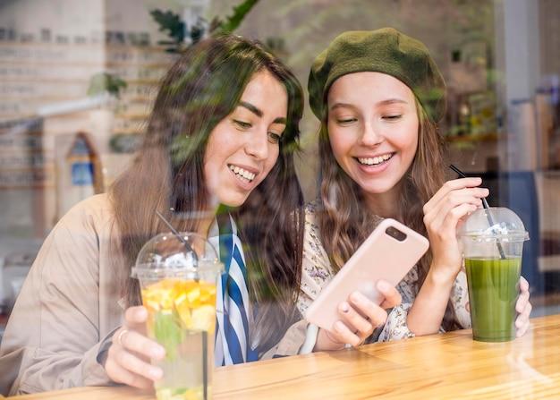 Mittlere schussfrauen mit frischen säften im café, das telefon betrachtet