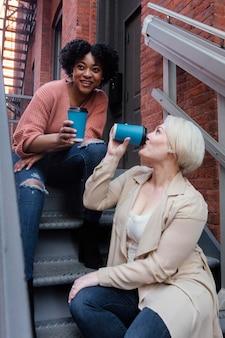 Mittlere schussfrauen mit kaffeetassen