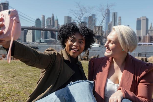 Mittlere schussfrauen mit kamera draußen