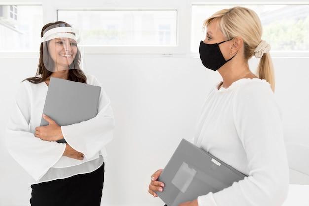 Mittlere schussfrauen mit maske und gesichtsschutz