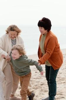 Mittlere schussfrauen und -kind am strand