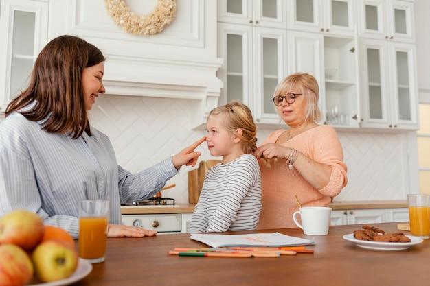 Mittlere schussfrauen und -kind in der küche