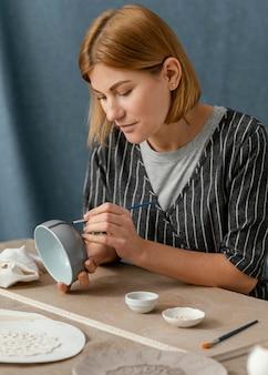 Mittlere schussfrauenmalerei mit pinsel