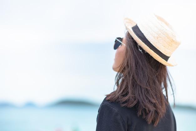 Mittlere schussfrauensonnenbräunehaut, die schwarzes hemd mit strohhut und sonnenbrille trägt. blick ins meer. am meer hintergrund. sommerreise. erholsam, urlaub und tropisch. alleinkonzept.