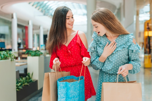 Mittlere schussfreunde mit einkaufstaschen