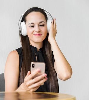 Mittlere schussgeschäftsfrau, die etwas musik auf kopfhörern genießt