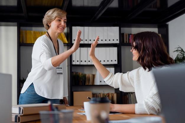 Mittlere schussgeschäftsfrauen hoch fünf
