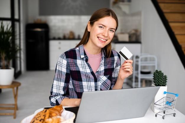 Mittlere schussglückliche frau, die kreditkarte zeigt