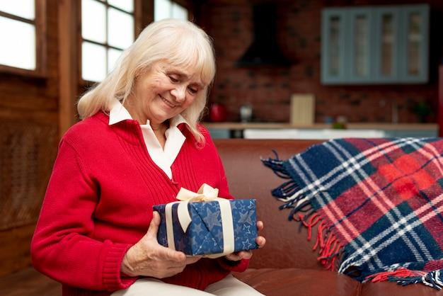 Mittlere schussglückliche großmutter, die ein geschenk hält