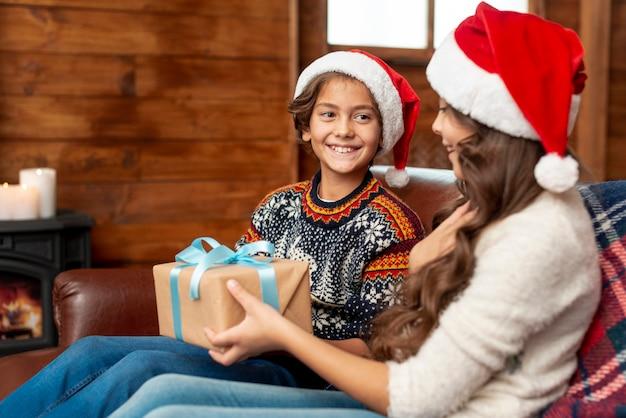 Mittlere schusskinder, die auf der couch mit geschenk sitzen